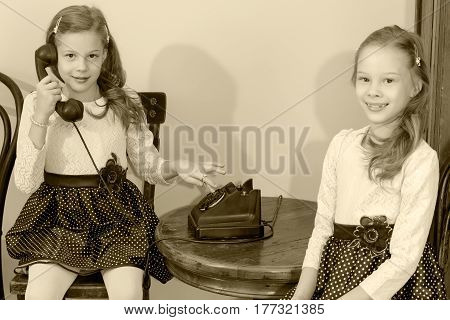 Two elegant girls sisters in beautiful dresses, talking on old phone. Black-and-white photo. Retro style.