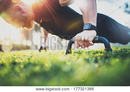 Healthy lifestyle concept.Training outdoors.Handsome sport man doing pushups in the park on the sunny morning. Blurred background