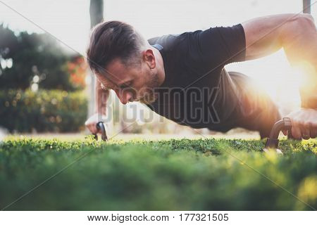 Muscular athlete exercising push up outside in sunny park. Fit shirtless male fitness model in crossfit exercise outdoors.Sport fitness man doing push-ups.Blurred background
