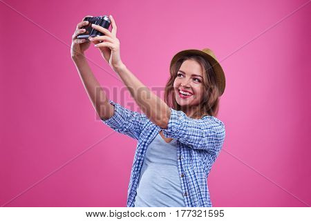 Close-up of elated casual girl making selfie with a silver vintage camera. Girl in straw hat and casual clothes