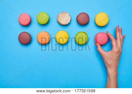 Female hand putting a colourful macaroon on the blue desktop with a copy space