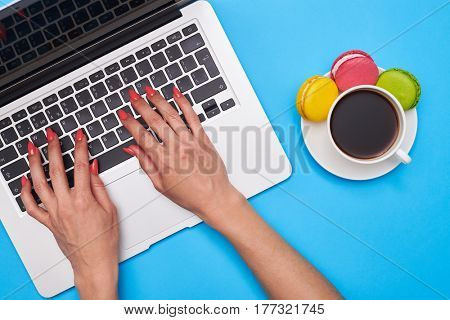 Top view of female hands pressing keys of black keyboard of the silver laptop. Delicious macaroons with a cup of coffee. Workplace
