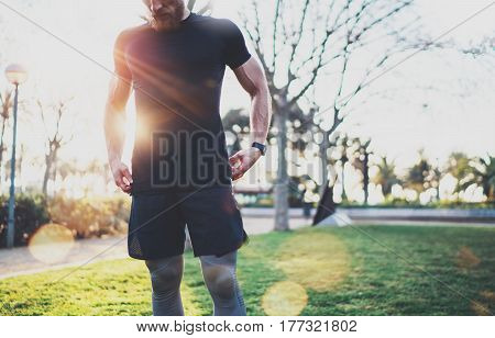 Workout lifestyle concept.Young man preparing muscles before training.Muscular athlete exercising outside in sunny park. Blurred background