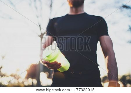Workout fitness concept.Muscular handsome athlete with protein milk shake cocktail after hard workout session on city park in the sunny morning.Blurred background