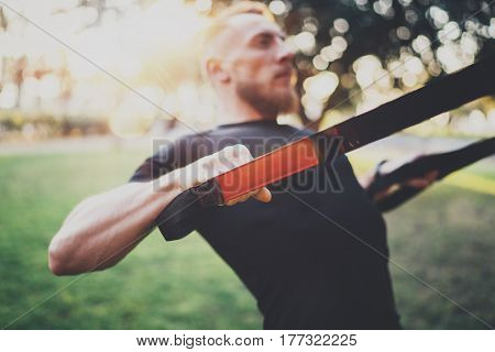 Muscular athlete exercising push up outside in sunny park at the morning.Attractive fittness man doing exercises outdoors.Blurred background.