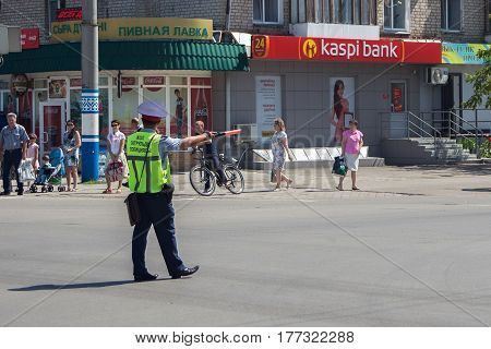 PETROPAVL, KAZAKHSTAN - JULY 24, 2015: The road police officer of Kazakhstan in uniform regulating traffic in the city. Petropavl is a city in northern Kazakhstan close to the border with Russia.