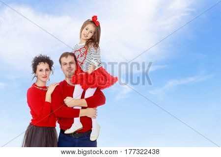 Happy young family dad mom and a little girl in bright red outfits . Dad holds daughter on hands.On the background of summer blue sky and fluffy clouds.