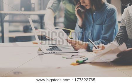 Group of young coworkers working together in modern coworking studio.Woman using smartphone for talking with partners about new startup project.Horizontal, color filter
