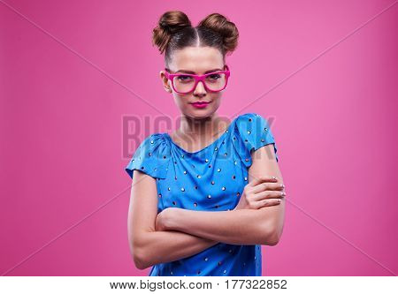 Close-up of slender girl in pink glasses with crossed hands over pink background. Brunette in colorful outfit posing against pink background
