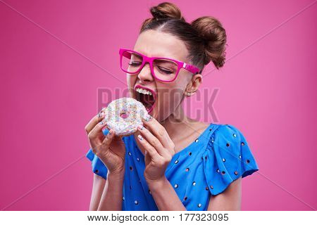 Close-up of trendy girl angrily biting a sprinkled doughnut. Trendy female with two buns in pink glasses