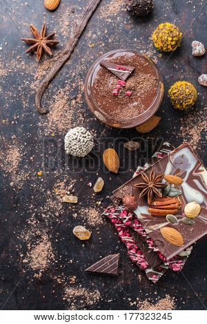 Sweet and treat, junk unhealthy food. Assortment of chocolate bar and praline truffle and mousse with spices and nuts on black moody grunge table. Flat lay top view overhead