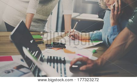 Group of young coworkers working together in modern coworking studio.Woman using smartphone talking with partners.Teamwork concept.Blurred background
