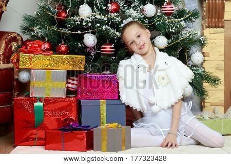 Cute little girl in white dress near a Christmas tree surrounded by boxes with gifts.