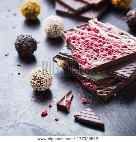 Sweet and treat, junk unhealthy food. Assortment of chocolate bar and praline truffle on black moody grunge table