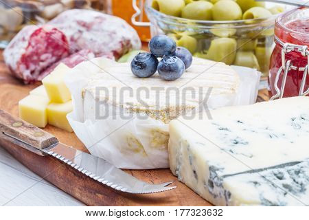 Wooden Cutting Board With Cheese, Cold Cuts And Jams
