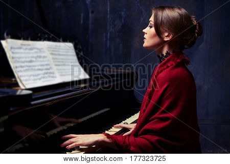 Mid shot of enchanted brunette with scarf over an evening dress playing sensibly the piano. Caucasian woman focusing on sheet music with notes while sitting down to the piano