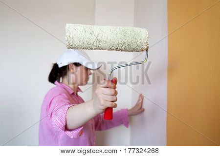 woman in a shirt holding a roller for painting and preparing to paint the wall