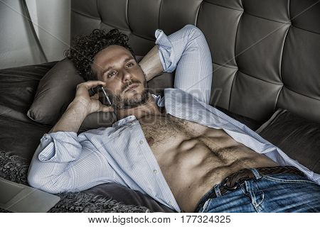 Shirtless sexy male model lying alone on his bed in his bedroom, looking at camera with a seductive attitude