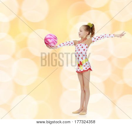 Cute little girl gymnast in a beautiful costume for competition, performs exercises with the ball.Brown festive, Christmas background with white snowflakes, circles.