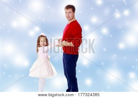 Cute little long-haired girl in a smart pink dress , reaches out to his dad.Blue Christmas festive background with white snowflakes.