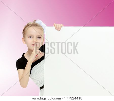 Beautiful little blonde girl dressed in a white short dress with black sleeves and a black belt.The girl peeks out from behind white banner.Pale pink gradient background.