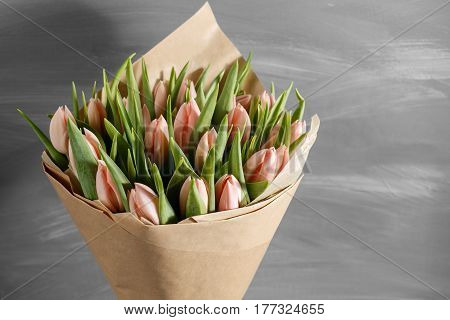 bouquet of pink tulips in a package of kraft paper, on gray wodden background.