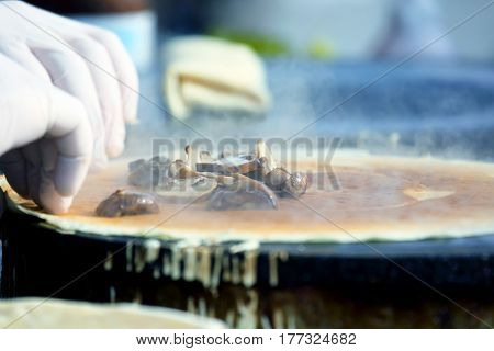 the a cooking pancakes stuffed with mushrooms