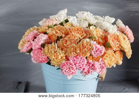 Pink, orange, white carnation flowers in blue bucket on old wood.