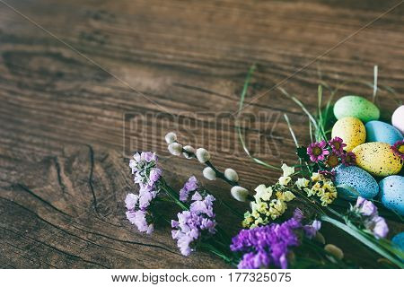 Easter background. Beautiful colorful eggs in nest with spring flowers over wooden dark background
