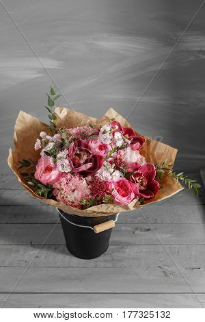 Bouquet of pink roses and Other colors flowers on wooden background, copy space