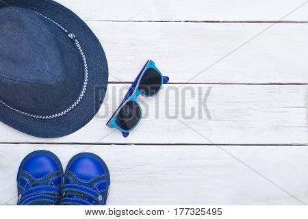 Kid's summer clothes On a white wooden background. Flat lay