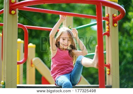 Cute Little Girl Having Fun On A Playground Outdoors