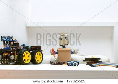 The robot holds a screwdriver in its hands to assemble the robot and next to it is a robot with wheels