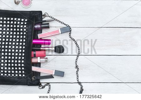 Female handbag and cosmetics lie on a wooden background. Flat lay