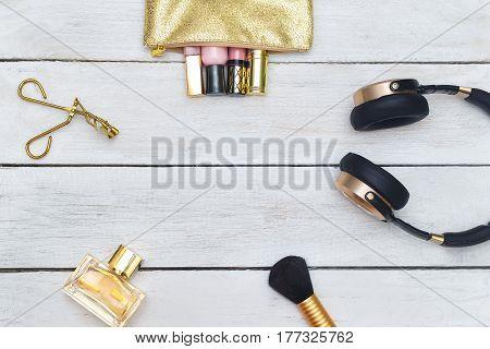 Feminine accessories gold: Lip gloss perfume headphones on Wooden background
