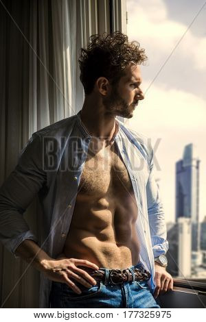Sexy man standing with shirt open on muscular chest in his bedroom next to window curtains