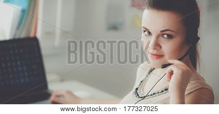 Beautiful business woman working at her desk with headset and laptop.
