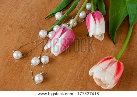 Tulips And White Pearls Lie On The Table