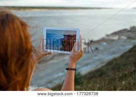 Back view of a young woman wanderer is making photo with portable tablet camera during her vacations in village meadows with great river. In reflection of the screen the smiling face of the girl is visible.