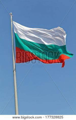 Bulgarian flag waving against blue sky