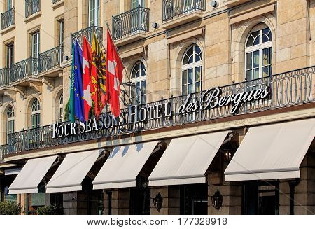 Geneva, Switzerland - 24 September, 2016: flags over the entrance to the Four Seasons Hotel des Bergues. Hotel des Bergues has been a landmark of the city of Geneva since 1834.