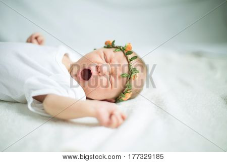 cute newborn baby in the wreath laying on the bed and yawns