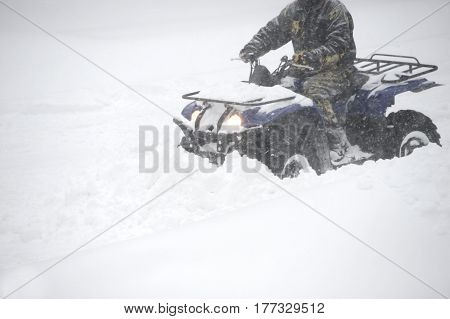 man removing snow with snowplow in blizzard