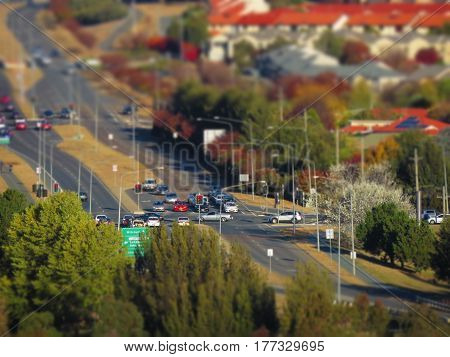 Bright and colourful mirco/toy like suburban city image showing cars trees, road houses and rooftops