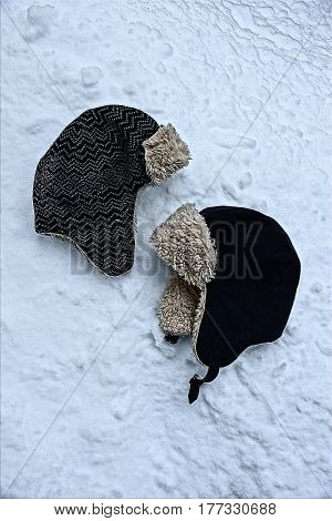Winter hats with earflaps in the snow