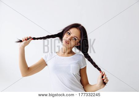 Young cheerful girl having fun. Smiling pretty woman makeup and hairstyle with pigtails. White background not isolated