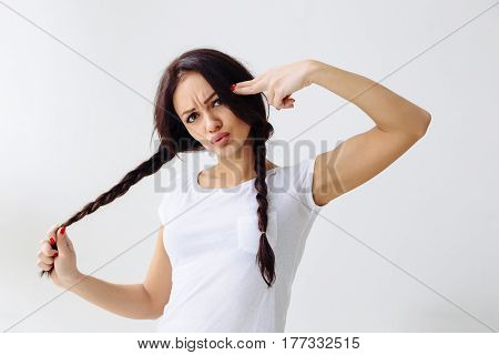 Angry young pretty woman gesturing with his fingers like a gun against temple. Are you crazy. Isolated on white wall background. Negative emotion facial expression feeling body language. Hairstyle with braid pigtails