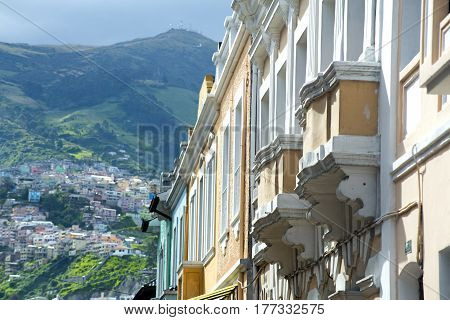Traditional Ecuadorian style houses and balconies with the city and the Pichincha mountain in the background