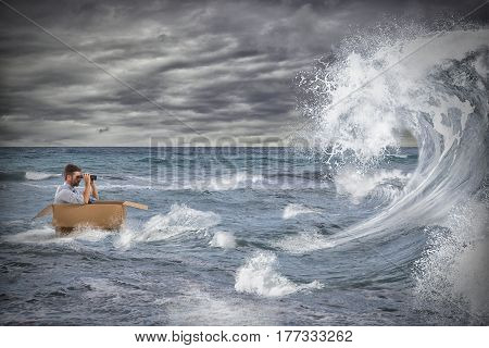 Businessman in a cardboard sails in a storm at sea. Deal with the crisis like a stormy sea concept
