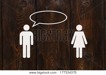 Paper woman and man is talking on wooden background. Dialog or conversation. Abstract conceptual image